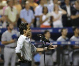 """El cantante Marc Anthony interpreta el himno """"God Bless America"""" en la séptima entrada del partido de béisbol de las Grandes Ligas que se jugó el martes pasado en Nueva York.   Matt Slocum / AP"""